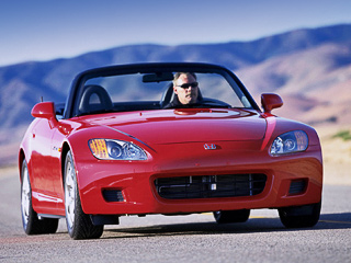 Honda s2000. Заднеприводный родстер S2000оснащается атмосферным мотором объёмом 2лмощностью 240л.с. (207Н•м). Коробка передач— только шестиступенчатая «механика», спомощью которой автомобиль разгоняется досотни за6,2с.