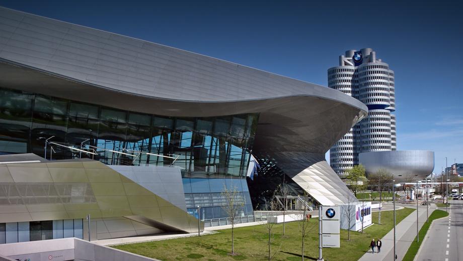 Bmw museum. Напереднем плане— комплекс BMW Welt. Подругую сторону шоссе отнего— головной офис компании ввиде четырёх цилиндров спримыкающим кнему зданием музея.