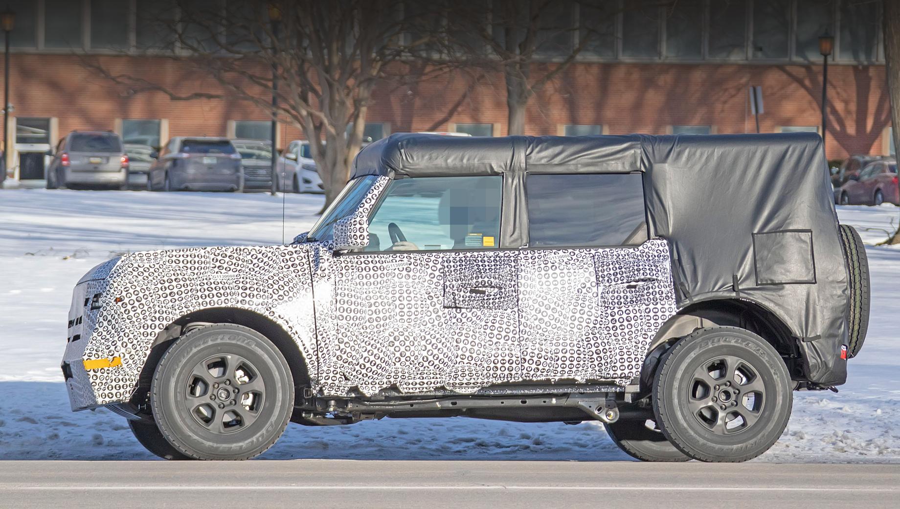 Ford bronco. Лобовое стекло установлено относительно близко к вертикали, форма передних крыльев и капота напоминает о линиях, присущих прежнему Bronco, особенно в восьмидесятых. Огромные накладки на крыше и задней стойке пока не позволяют оценить силуэт.