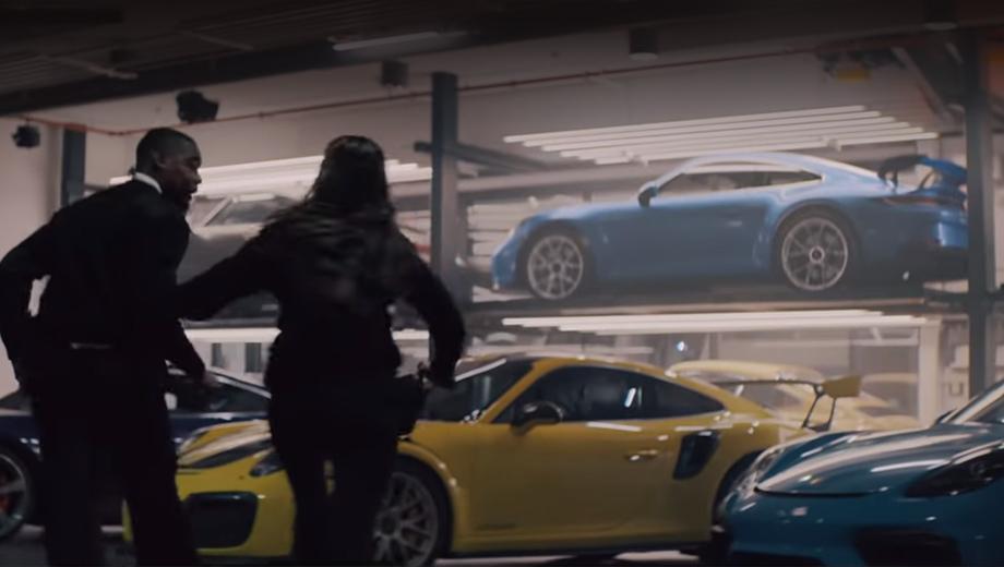 Porsche 911,Porsche 911 gt3. Быстрый атмосферный монстр (синее купе на втором ярусе) появляется в кадре на несколько секунд как камео, мгновенно распознанное фанатами бренда. Обратите внимание на сочетание «утиного хвостика» и высоко поднятого антикрыла.