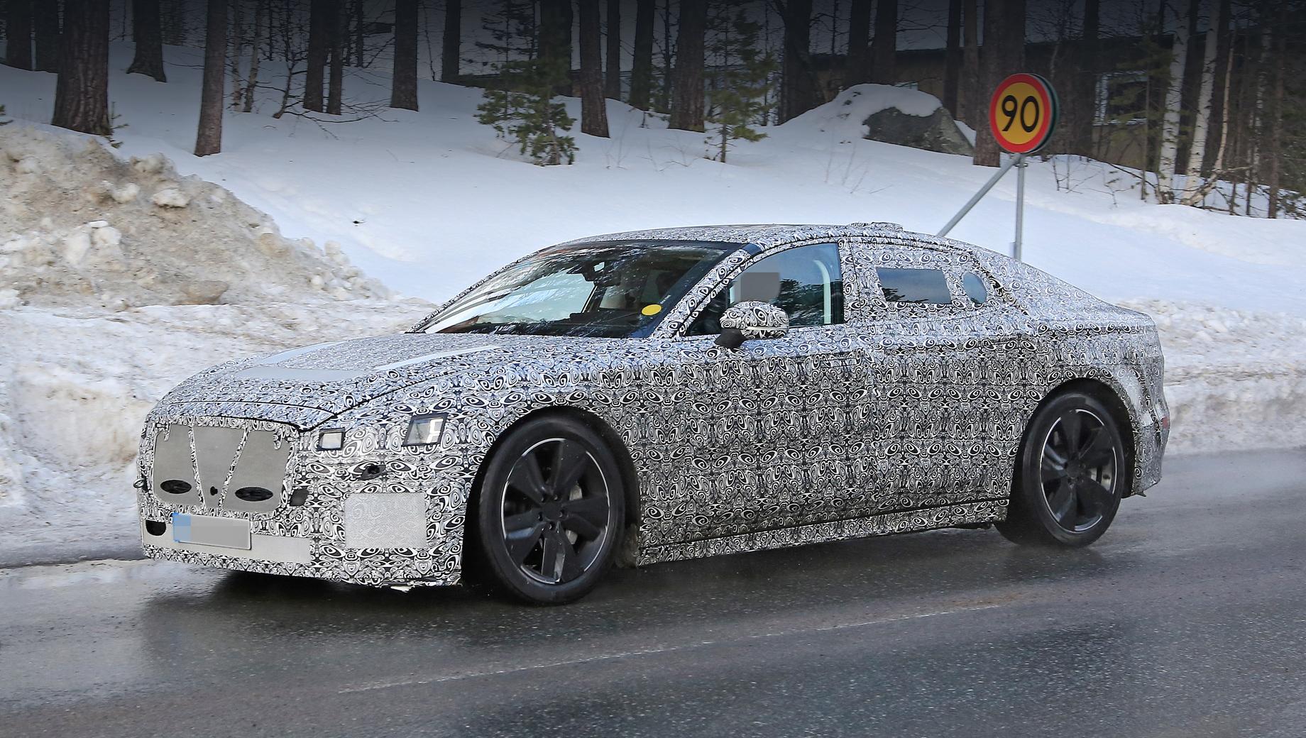 Jaguar xj. Несмотря на обильную маскировку, о новом кузове «икс-джея» сказать можно многое: тут очень узкое остекление, стеклянный треугольник в передних дверях, зеркала с креплением на панели двери, а не в углу стекла. Широкие спицы колёсных дисков оптимизированы явно с точки зрения аэродинамики.
