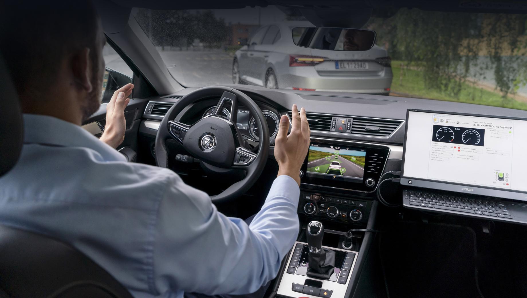 Skoda superb. По снимку с испытаний кажется, что перед нами очередной банальный автопилот, но не всё так просто. Шкода, чей интерьер мы видим, откликается на действия водителя автомобиля, едущего первым.