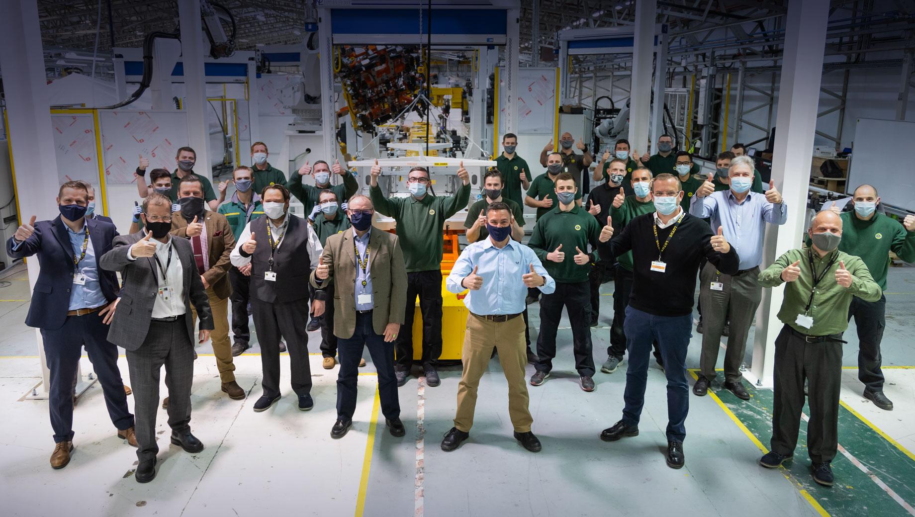 Lotus emira. Команда Лотуса во главе с Мэттом Виндлом радуется старту производства Эмиры, скрывая саму виновницу торжества. Впрочем, для радости есть и другие поводы. Под крылом Geely штат почти удвоился, а Emira создала более 200 рабочих мест. Идёт набор персонала.
