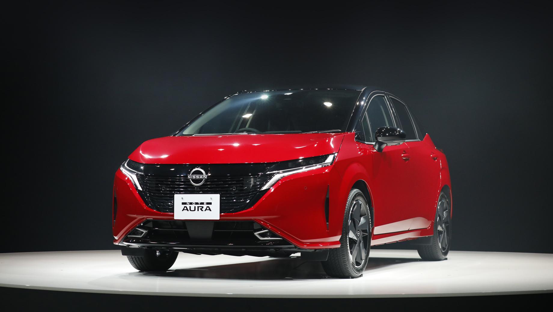 Nissan note,Nissan note aura. Носовую часть гибридного хэтча дизайнеры сделали похожей на электрический паркетник Ariya. Потому тут появились более узкие, чем на Ноуте, фары, перекроенный бампер, чёрная решётка радиатора с множеством трапециевидных элементов.